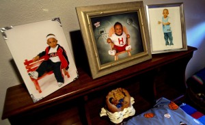 Photographs of Titches Lindley sitting above his bed at the home of his father, William Wade, in Dallas. Photograph by Melanie Buford for The Dallas Morning News