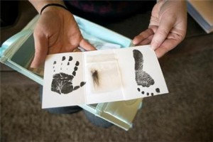 Jennifer Blaz, 34, holds the small hand print, hair clipping and footprint given to her by the hospital after her daughter Mattisyn Blaz's death in 2013. Her husband, Matthew Blaz, was convicted of killing her daughter. / AP photo